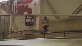 De rolschaatser maakt gevaarlijke dia op lange omheining in skatepark springplank uitdaging competition stock footage