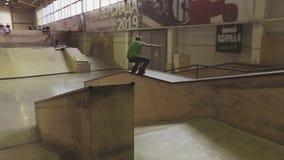 De rolschaatser maakt stunt op rand van springplank op uitdaging in skatepark competition wedstrijd stock videobeelden
