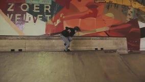 De rolschaatser met sprong over omheining, misstap op springplank, maakt dubbele tik in skatepark competition stock footage