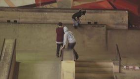 De rolschaatser versnelt, maakt stunts op springplank op wedstrijd in skatepark uitdaging competition stock videobeelden