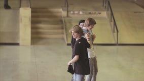 De rolschaatsers geven vijf aan elkaar op wedstrijd in skatepark uitdaging competition Glimlach stock videobeelden
