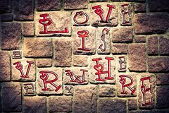 De romantische achtergrond op een concrete bakstenen muur en een rode liefde is hierboven overal geïmponeerd stock afbeelding
