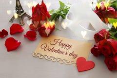 De romantische achtergrond van de valentijnskaartendag met mooi boeket van rozen en maskerade wit masker op houten lijst stock afbeelding