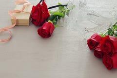 De romantische achtergrond van de valentijnskaartendag met mooi boeket van rozen en maskerade wit masker op houten lijst royalty-vrije stock afbeelding