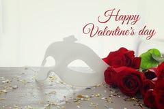 De romantische achtergrond van de valentijnskaartendag met mooi boeket van rozen en maskerade wit masker op houten lijst stock fotografie