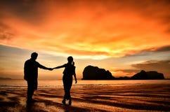 De romantische handen van de paarholding bij zonsondergang op strand royalty-vrije stock afbeeldingen