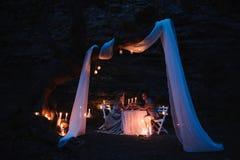 De romantische handen van de paarholding samen over kaarslicht tijdens romantisch diner in openlucht stock foto