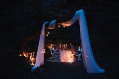 De romantische handen van de paarholding samen over kaarslicht tijdens romantisch diner in openlucht stock foto's