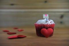 De romantische kopcake in roze en het wit met een miniatuurpersoonsbeeldje die een teken houden schepen op hoogste en rode liefde stock foto