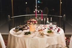 De romantische lijst die met wijn, mooie bloemen in vakje plaatsen, lege glazen, nam bloemblaadjes en kaarsen toe stock afbeeldingen