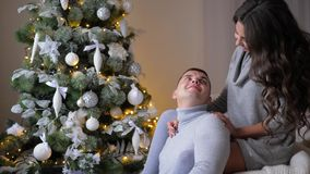 De romantische ogenblikken, meisje zitten op laag en dichtbij het koesteren van echtgenoot aan spar op vooravond van Kerstmis stock footage