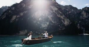De romantische paarclose-up in het midden van meer in de houten boot de man roeit en zijn meisje die met benen spelen stock footage