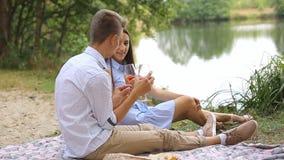 De romantische picknick van jongelui koppelt in liefde in het bos dichtbij het meer stock video