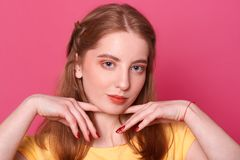 De romantische tedere jonge dame houdt de vingers met rode manicure dichtbij leuk vers gezicht met omhoog het stellen over donker stock afbeelding
