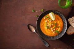 De romige soep van de wortelkikkererwt op donkere rustieke achtergrond stock foto