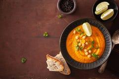 De romige soep van de wortelkikkererwt op donkere rustieke achtergrond stock fotografie