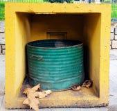 De ronde bak van het metaalvuilnis in een vierkante concrete doos stock afbeeldingen