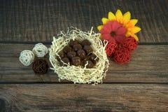 De ronde chocolade in een nest van stro, multicolored decoratieve ballen en bloem ontluikt op een houten lijst royalty-vrije stock foto