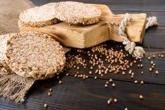 De ronde dieetbroden van luchtig boekweit op houten achtergrond met boekweit verspreidden zich rond, uitstekende raad en jute stock afbeelding
