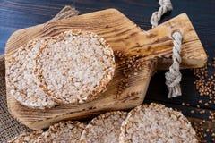 De ronde dieetbroden van luchtig boekweit op houten achtergrond met boekweit verspreidden zich rond, uitstekende raad en jute Hoo royalty-vrije stock afbeeldingen
