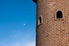 De ronde rode toren van het baksteenblok met rond venster in blauwe duidelijke hemel stock foto's