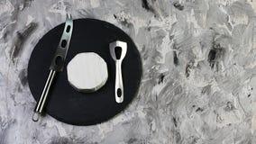 De ronde witte kaascamembert of de Brie op een ronde schalie scheept het proeven met messen voor kaas in - Melkproductie Exemplaa Stock Fotografie