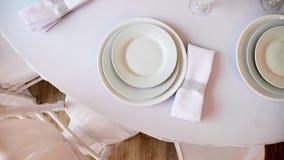 De rondetafel met een wit gediend tafelkleed plateert wijnglazen en servetten stock video