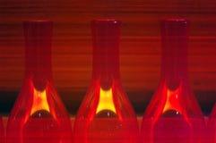 De rood licht verlichte abstracte achtergrond van glasflessen Stock Foto