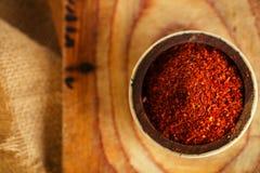 De roodgloeiende vlokken van de Spaanse peperspeper in kom op houten raadsbackgro Stock Foto