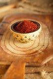De roodgloeiende vlokken van de Spaanse peperspeper in kom op houten raadsbackgro Royalty-vrije Stock Foto