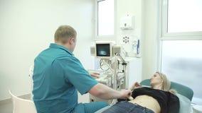 De roodharige arts houdt een diagnose van de vrouwenultrasone klank van de maag stock footage