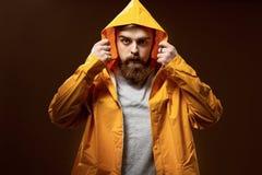 De roodharige kerel met een baard en een snor gekleed in een grijze t-shirt en het gele jasje met een kap stellen op een bruin royalty-vrije stock fotografie