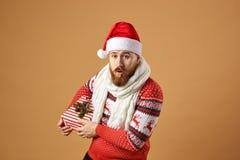 De roodharige mens met baard kleedde zich in een rode en witte sweater met herten, witte gebreide sjaal en een hoed van Santa Cla stock afbeeldingen
