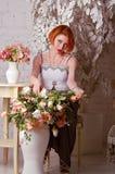 De roodharige vrouw met bloemen Stock Afbeeldingen