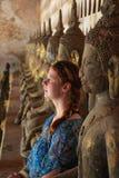 De roodharige witte jonge vrouw zit op de achtergrond van de standbeelden van Boedha in de tempel stock foto's