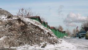 De rook die uit schoorsteen van het centrale heatiing komen plant en oud industrieel landschap met vuile sneeuw en roestige daken stock video