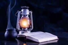 De rook en het gaslantaarn van de heksen zwarte pot en open boek op donkere en mistige achtergrond royalty-vrije stock fotografie