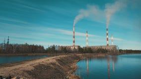 De rook komt uit de pijpen van de waterkrachtcentrale Op de achtergrond is een blauwe hemel met wolken stock video