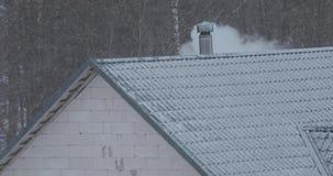 De rook komt uit de schoorsteen op het dak van het huis in de winter stock video