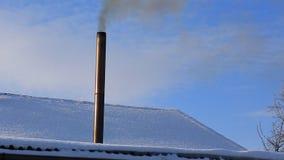 De rook komt uit de schoorsteen van het huis De pijp op het dak Het huis met een schoorsteen Rook in de blauwe hemel stock video