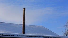 De rook komt uit de schoorsteen van het huis De pijp op het dak Het huis met een schoorsteen Rook in de blauwe hemel Tijd stock videobeelden