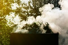 De rook trekt zich van het vat terug wanneer het gras in de gekleurde tuin wordt gebrand, prachtig royalty-vrije stock afbeeldingen
