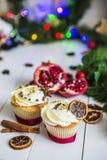 De roomcakes, cupcakes snijden rode granaatappel, kaneel, liggen de droge citroenen op witte houten lijst Royalty-vrije Stock Foto's