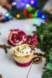 De roomcakes, cupcakes snijden rode granaatappel, kaneel, liggen de droge citroenen op witte houten lijst Stock Foto's