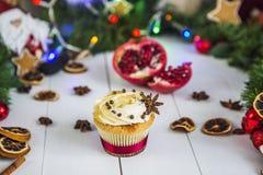 De roomcakes, cupcakes snijden rode granaatappel, kaneel, liggen de droge citroenen op witte houten lijst Stock Afbeelding