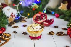 De roomcakes, cupcakes snijden rode granaatappel, kaneel, liggen de droge citroenen op witte houten lijst Royalty-vrije Stock Afbeelding