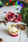 De roomcakes, cupcakes snijden rode granaatappel, kaneel, liggen de droge citroenen op witte houten lijst Royalty-vrije Stock Afbeeldingen