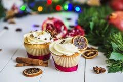 De roomcakes, cupcakes snijden rode granaatappel, kaneel, liggen de droge citroenen op witte houten lijst Royalty-vrije Stock Fotografie
