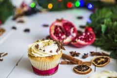 De roomcakes, cupcakes snijden rode granaatappel, kaneel, liggen de droge citroenen op witte houten lijst Stock Fotografie
