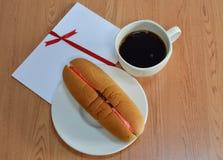 De roomrozijn van de hotdogbrood gevulde aardbei en zwarte koffie Stock Foto's